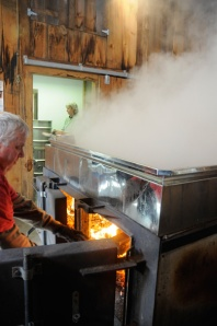 Steve stokes the fire under the evaporator to keep up a steady boil